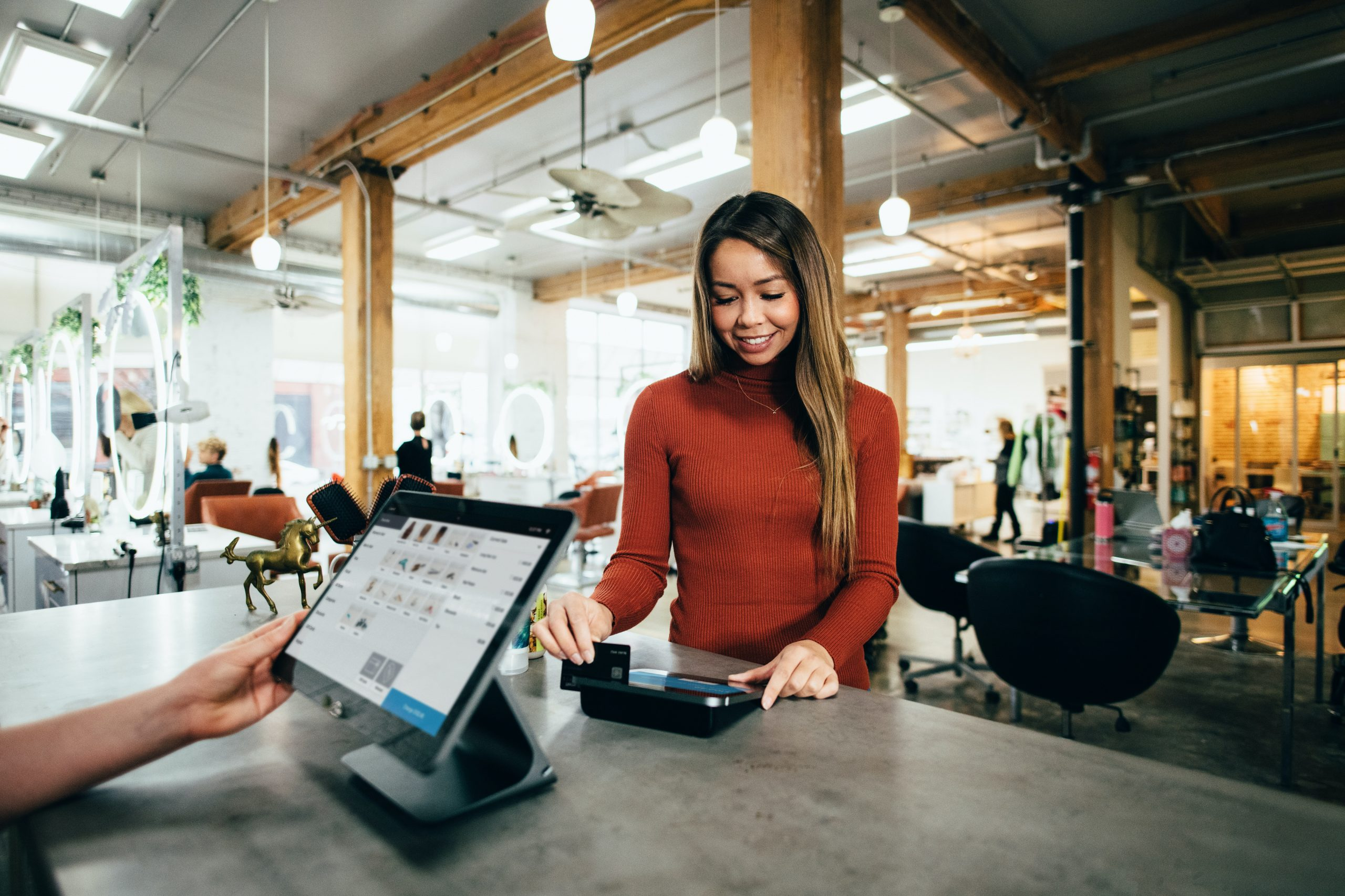 Woman in orange sweater using credit card at hip cafe